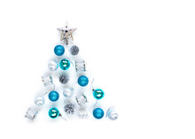 Christmas Tree Decorative Ornaments Of Silver Star, Blue Balls, Pine Cone, Tinsels And Drums Over White Background Arranged In Pine Tree Shape With Copy Space For Winter Merry X'mas Text Insertion