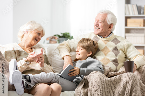 Grandmother and grandfather siting on couch with their grandson, reading a book