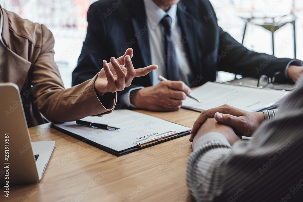 Fototapeta Two senior manager reading a resume during a job interview, Employer interviewing to ask young male job seeker for recruitment talking in office