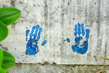 Blue Handprints On A Concrete Wall