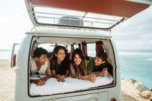 Young People Enjoy Holiday Lay Down Relax Inside Vintage Van