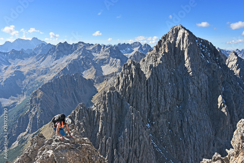Fotografiet  Female climber with helmet and backpack climbing in a wild rocky landscape with steep mountains under blue sky at a beautiful day in autumn