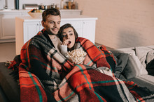 Beautiful Young Couple Watching Movie With Popcorn On Couch And Covering With Plaid