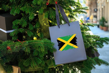 Jamaica Flag Printed On A Christmas Shopping Bag. Close Up Of A Shopping Bag As A Decoration On A Xmas Tree On A Street. New Year Or Christmas Shopping, Local Market Sale And Deals Concept.