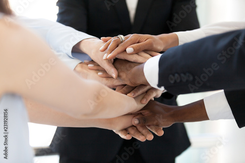Fotografía  Close up of diverse employees stack hands in pile show mutual support, multiethn