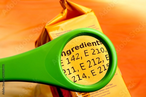 Fotografia Concept of reading ingredients list on food package with magnifying glass