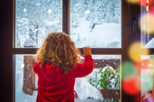 Little Girl Looking At The Snow Through The Window
