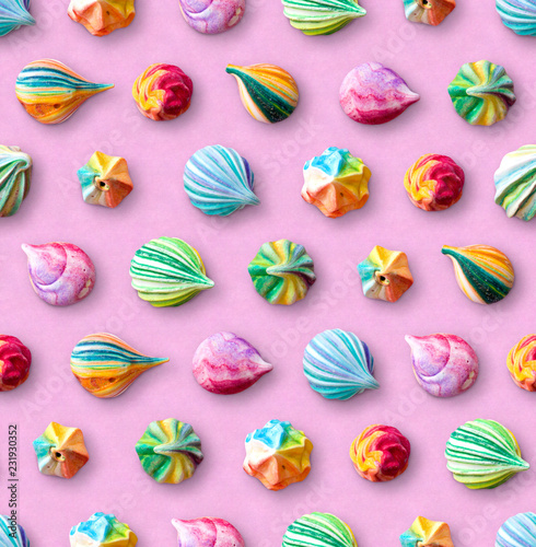 Seamless pattern of multicolored meringues. Colorful little meringue cakes on a pink pastel background.
