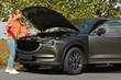 Woman near broken car on road. Auto insurance