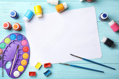 Flat lay composition with empty paper and painting supplies for child on table. Space for text