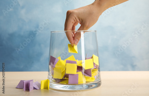 Obraz Woman taking paper piece from glass vase on table. Lottery - fototapety do salonu