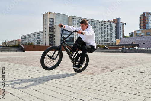 Photo Full length portrait of modern young man doing stunts on bmx bike in parking lot