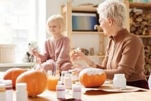 Cheerful Family Painting Pumpkins