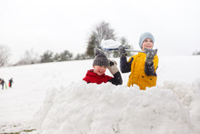 Snow Battle In The Fortress. Children Throw Snowballs In The Park.