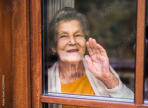 An elderly woman standing by the window, looking out Fototapet