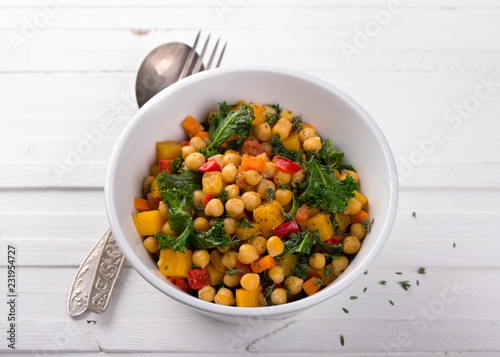 Homemade ragout with pumpkin, carrots, sweet peppers, tomatoes, chickpeas, kale and thyme in a white bowl on a white background. delicious healthy food