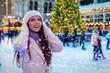 canvas print picture - Junge Frau in winterlicher Kleidung auf einem Weihnachtsmarkt freut sich über den Schneefall