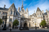 Fototapeta Londyn - Bright afternoon view of the gothic architecture of the Royal Courts of Justice Building under blue sky in London, England, UK