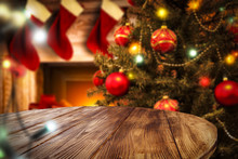 Table Background Of Free Space For Your Decoration. Christmas Tree With Balls And Fireplace Background With Few Christmas Sacks.