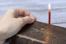 Female Hand On Holy Bible Dook And Burning Red Church Candle Behind