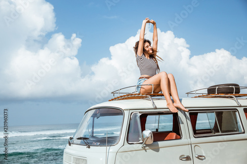 Fotografie, Obraz  Beautiful woman enjoy road trip nature sitting on the roof