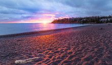 Brilliant Sunrise Of Lake Superior In Northern Minnesota. Red Orange Reflecting On Sandy Beach With Sun Peeking Through Clouds And Trees.