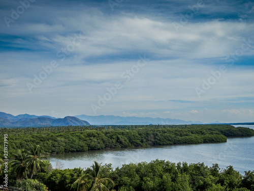 beautiful view of the Cuyutlan lagoon with green vegetation with a blue sky with white clouds in a wonderful tropical day in Manzanillo Colima Mexico