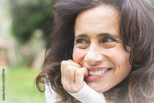 Lovely middle aged woman with playful look bites her nails with smile on blur background Fototapet