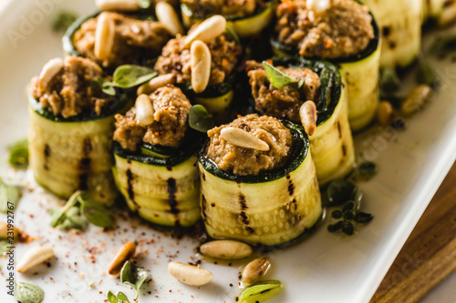 Fototapeta vegan appetizer of grilled zucchini and olive pate on a festive table