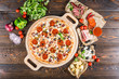 Large meat pizza with bacon, sausage, salami, pepperoni and olives and on a round cutting board on a dark wooden background. Pizza ingredients