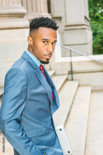 d351b3c36c After work. Young African American Businessman with beard, short afro hair,  working in New York, wearing dark sky blue suit, violet patterned tie, ...
