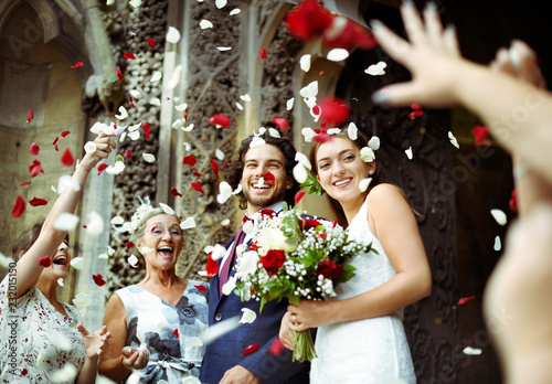 Family throwing rose petals at the newly wed bride and groom Fotobehang