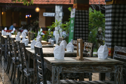 Tuinposter Asia land Empty wooden restaurants chairs and tables in the garden, evening time before dinner, no people