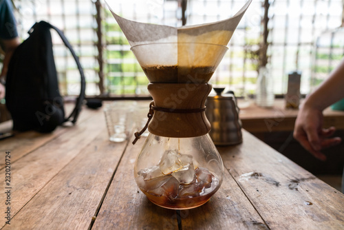 Glass bottle with ice to make ice drip coffee, on wooden table, vintage style Poster Mural XXL