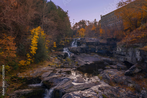 Fotografie, Obraz  autumn waterfall scene with trees and old building in background