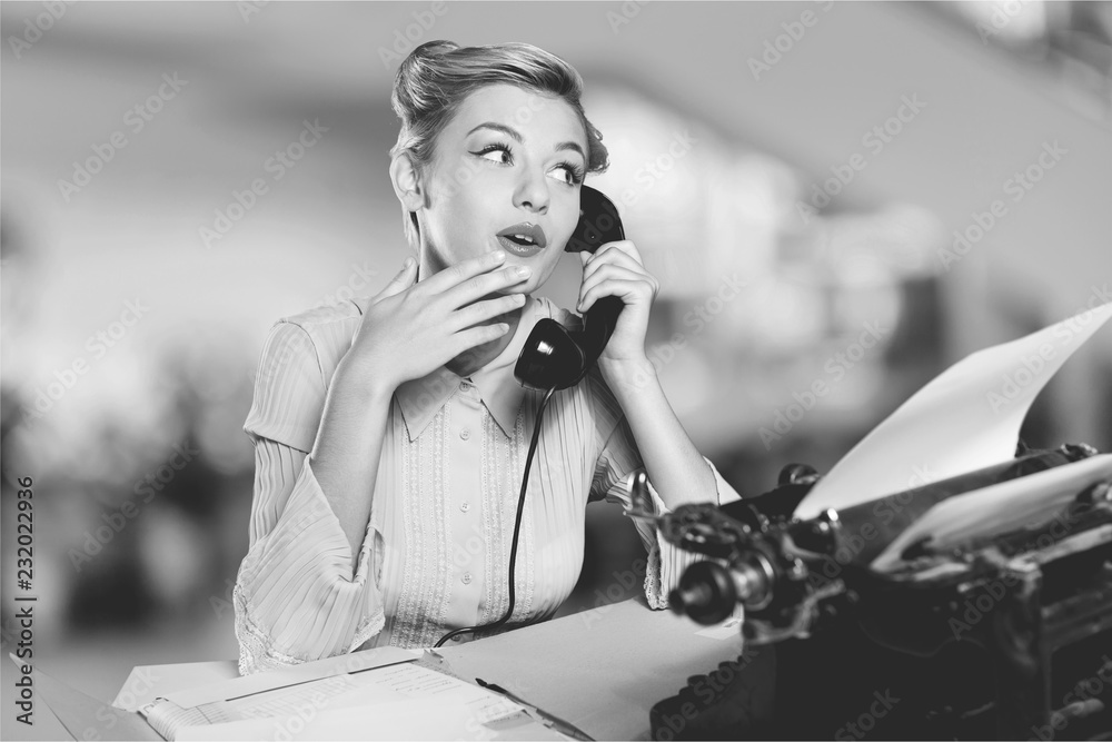 Fototapeta Attractive young woman speaking on  vintage phone