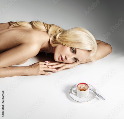 Calm, nude lady lying on the bright floor and looking at the cup of coffee
