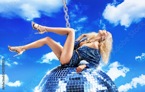 Conceptual picture of a lady swinging on disco ball