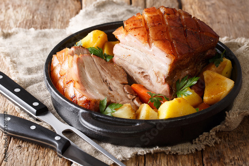 German recipe crispy pork served with vegetables and gravy close-up in a pan on the table. horizontal