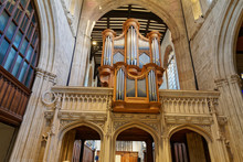 Great Pipe Organ Under Arched Ceiling In Old Catholic Church In England. View From Below. Largest Musical Instrument Mostly Used In Church Service In Western Countries.