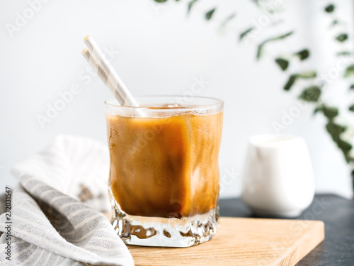Photo Refreshing iced latte coffee in a glass with straws in a modern kitchen