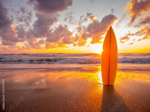 Foto op Plexiglas Zee zonsondergang surfboard on the beach in sea shore at sunset time with beautiful light