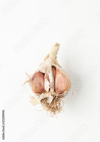 Fotografía  Half raw garlic with root on white background