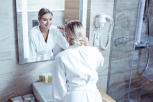 Woman Wearing White Bathrobe Brushing Teeth Before Going To Bed