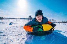 Man Snow Tubing From Hill. Winter Activity