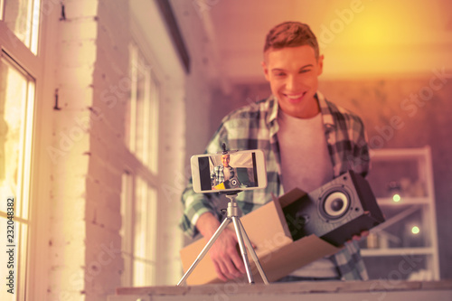 Fotografía  Joyful young blogger showing item hes opening