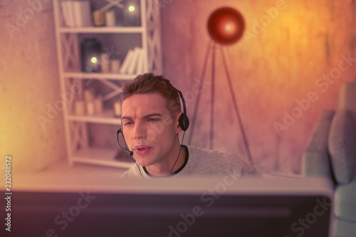 Bemused gamer looking on the screen of computer Wallpaper Mural