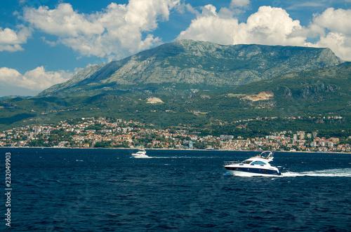 Moving white yachts on Boka Kotor bay near Herceg Novi, Montenegro