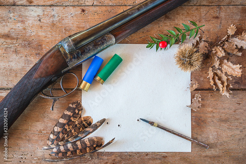 Foto op Canvas Jacht Beautiful hunting season still life/vintage hunting rifle, cartridges, vintage pen on the target with traces of bullets, pheasant feathers on old wooden background