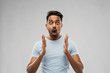 emotion, expression and people concept - scared man in t-shirt over grey background